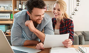 Young Couple Laughing and Enjoying Going Over Finances