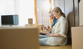 Couple Sitting on Floor After Move In Eating Take Out