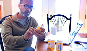 Senior Looking Intently at Medication Bottle