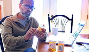Senior Looking Intently at Medication Bottle