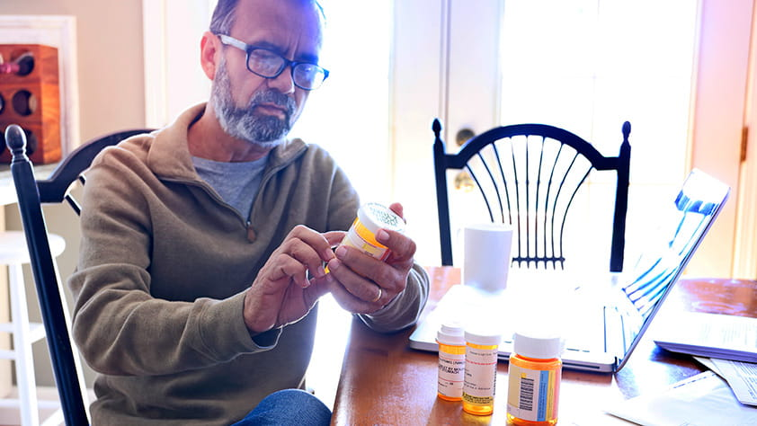 Older man looking at a prescription bottle