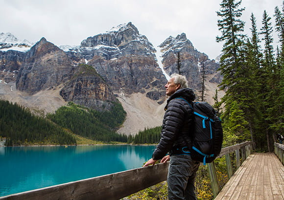 Senior Man Wearing a Hiking Backpack Standing on Boardwalk Admiring Mountain
