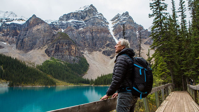 Senior Man Wearing a Hiking Backpack Standing on Boardwalk Admiring Mountain - Freebies and Discounts Especially for Seniors
