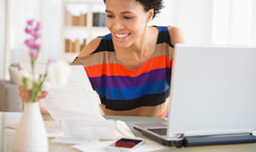 Young African-American woman in a striped shirt working on her laptop and looking at paper documents
