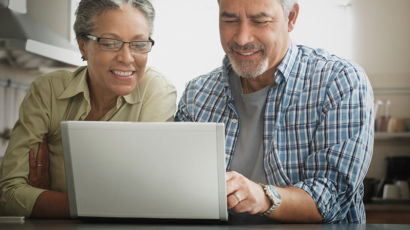 Older couple smiling and looking at computer