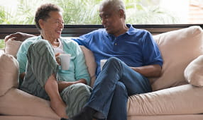 Senior couple sitting on a tan sofa, drinking a hot drink and having a conversation