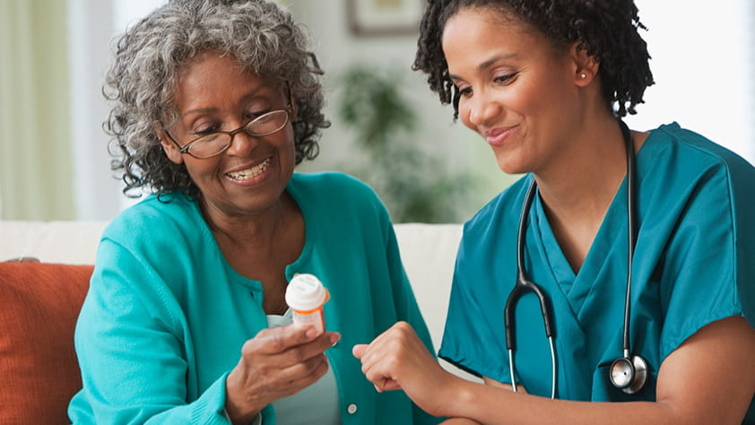 Senior woman and a nurse looking at a medicine bottle