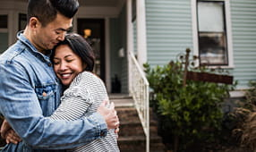 Couple Embracing Outside of Home