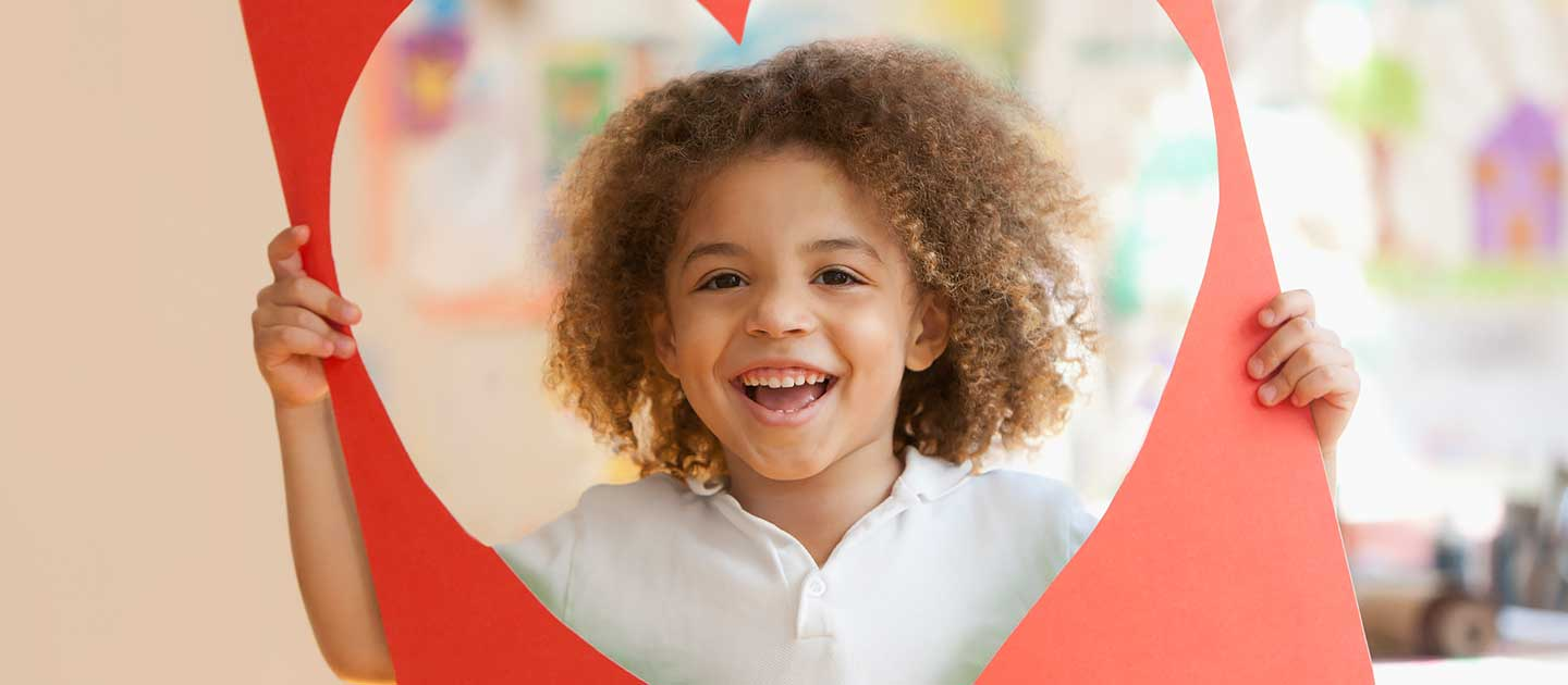 Grinning Young Boy Looking Through a Large Red Construction Paper Heart-Shaped Cut-Out