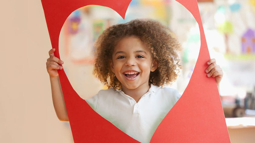 Celebrating Teacher Appreciate Week - Grinning Young Boy Looking Through a Large Red Construction Paper Heart-Shaped Cut-Out