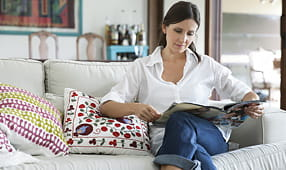 Woman Sits on a Couch Reading a Magazine