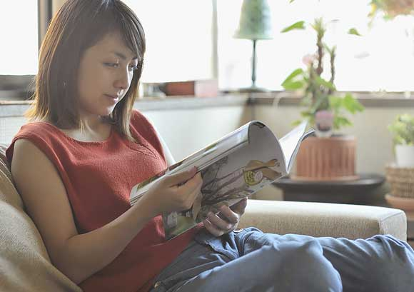 Young Woman Reading a Magazine to Help Keep New Year's Resolutions
