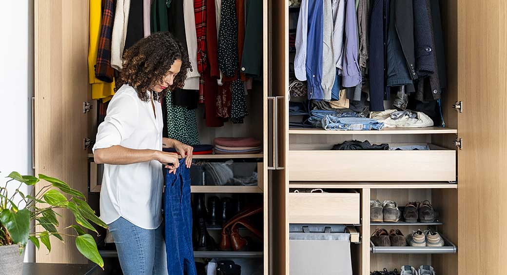 Woman Putting Clothes Into Her Well-Organized Closet