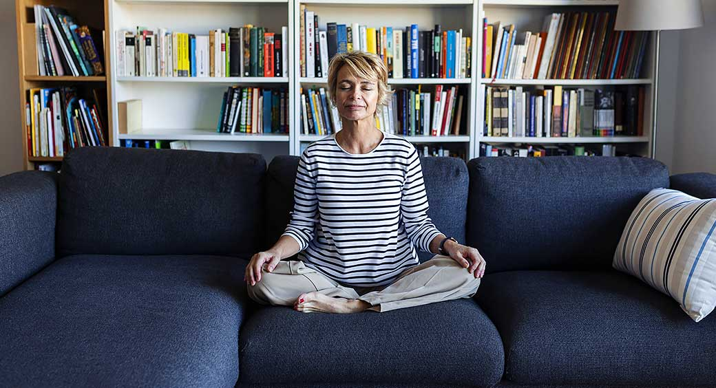 Woman Sitting on a Couch Meditating for Her New Year's Resolution to Care for Her Mental Wellness
