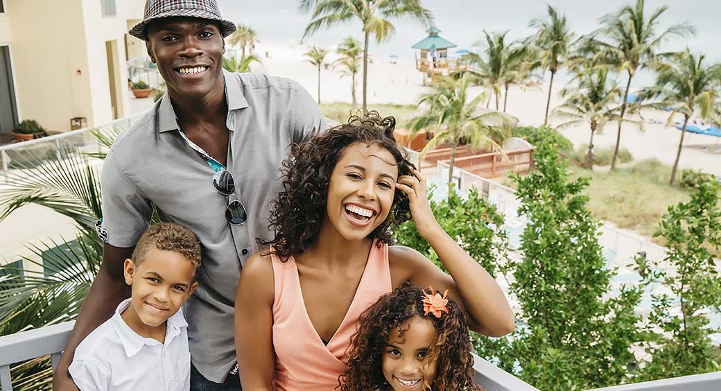 Young Family Vacations at a Resort Near a Beach and Palm Trees