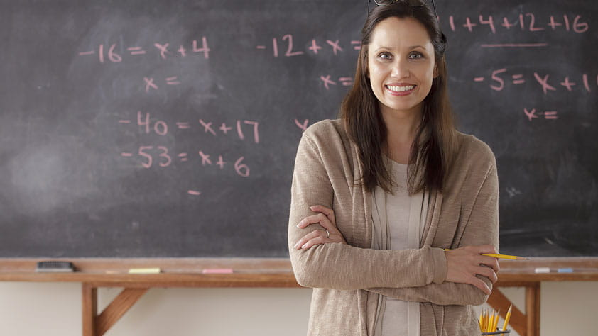 Portrait of a Teacher in Front of a Blackboard - Save a Bundle with Your NEA Member Benefits Teacher Discounts