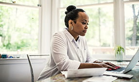 Woman at home working on laptop computer