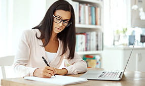 Young Woman Using a Laptop and Writing Notes