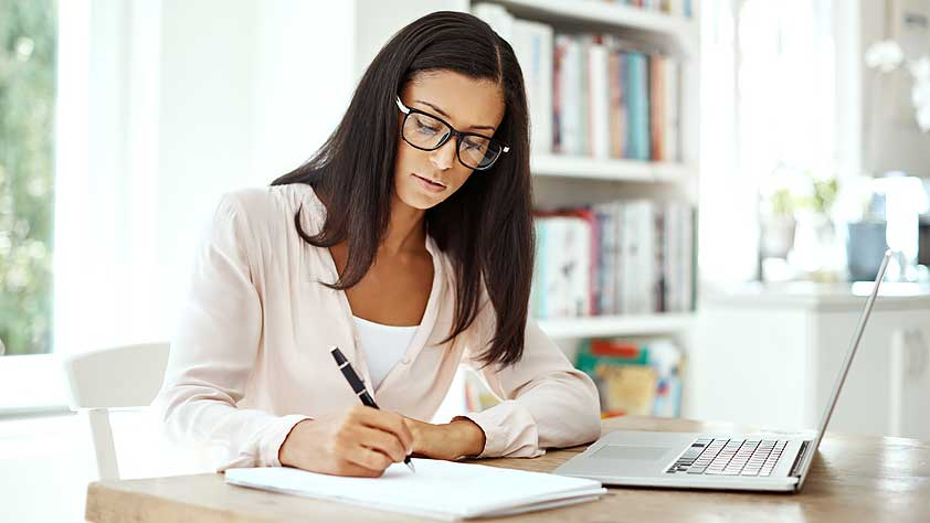 Should I Refinance My Student Loans - Young Woman Using a Laptop and Writing Notes