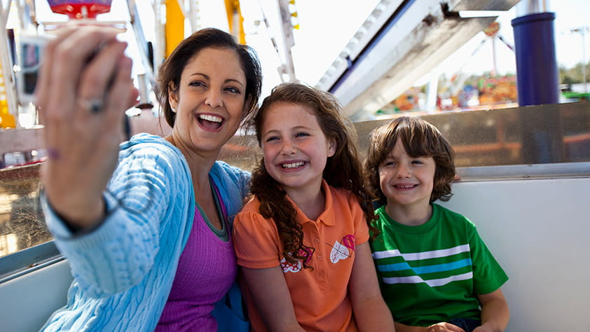 Mother taking a selfie with her daughter and son while riding on a Ferris wheel