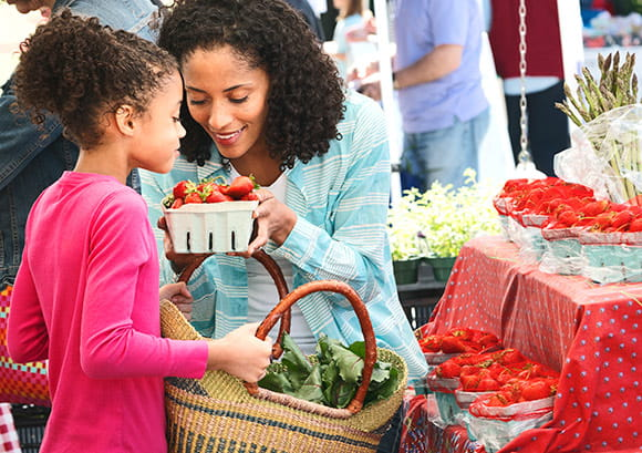 Mom Handing Daughter a Bushel of Strawberries
