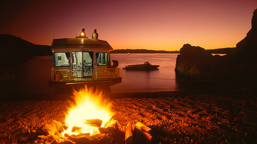 Houseboat camper at sunset with a campfire in foreground and a water-ski boat in the background