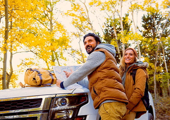 Hikers Leaning on a Car Hood Reading a Map