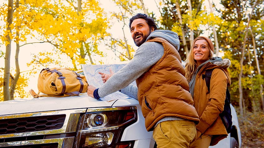 3 Leisurely Drives for Spectacular Fall Color - Hikers Leaning on a Car Hood Reading a Map