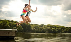Two Young Girls in Swimsuits Jumping off a Dock into a Lake