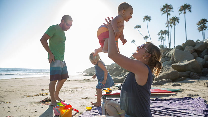 Young family of four playing on a sunny beach with palm trees in the background