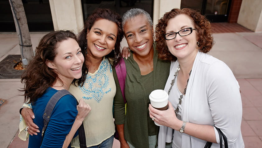 Group of four smiling women standing on a city sidewalk