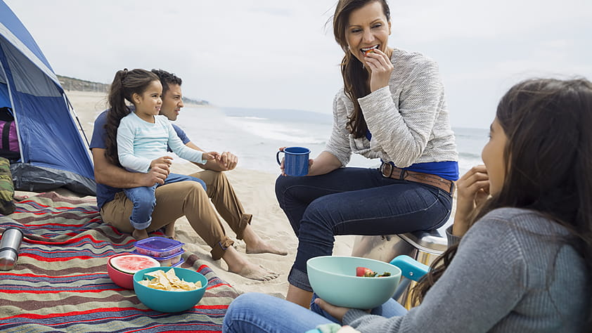 Family picnicking outside their tent on the beach