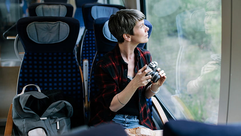 An older female backpacker enjoying the scenery and taking photos during a train journey