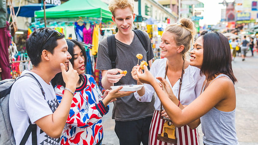 Group of friends tasting local food at a street festival