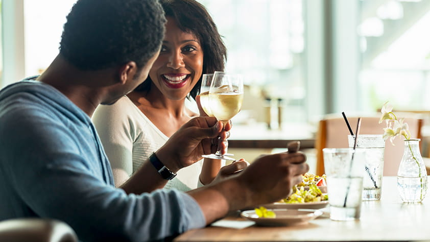 Smiling African-American couple drinking wine and enjoying a meal in a café