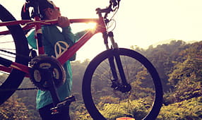 Woman carrying her mountain bike toward a sunrise ride on a wooded trail