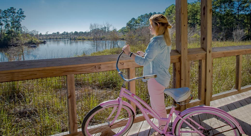 Woman on a pink bike looking out over wetlands in Tammany Trace, Covington to Slidell, Louisiana