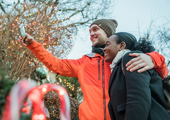 Couple Taking a Selfie in Front of a Holiday Lights Display