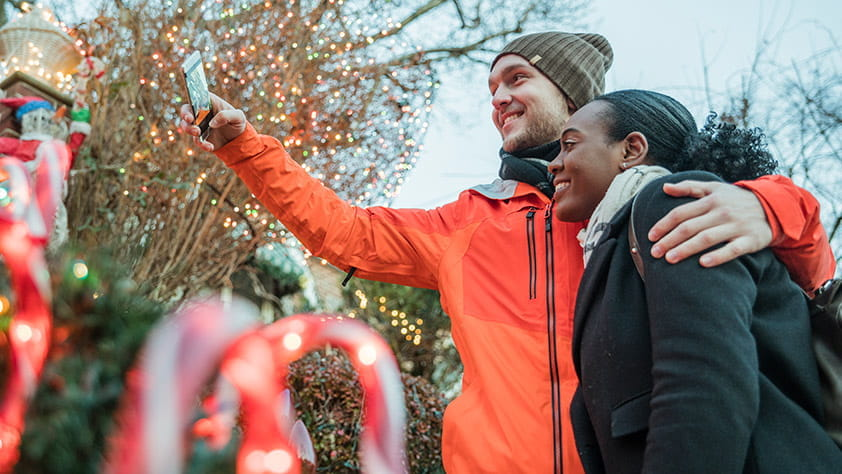 5 U.S. Towns Wrapped in Holiday Spirit - Couple Taking a Selfie in Front of a Holiday Lights Display