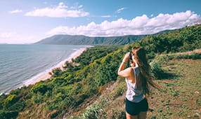 Woman Looking Over Ocean View with Binoculars
