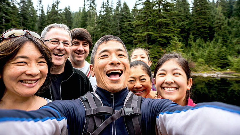 Extended family taking a selfie while hiking in the woods