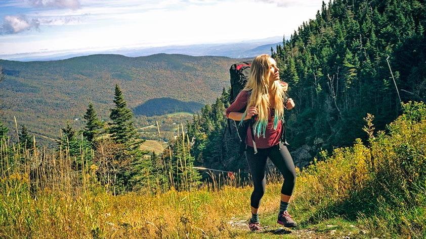 Woman hiking on a rocky ridgeline in New England