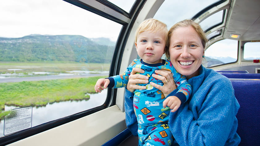 Mother and toddler son riding on a train