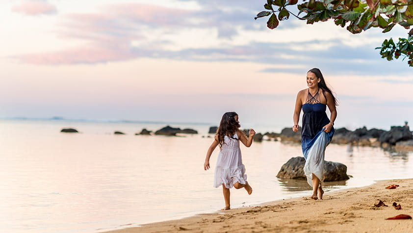 Mother and daughter playing together on a beach in Hawaii