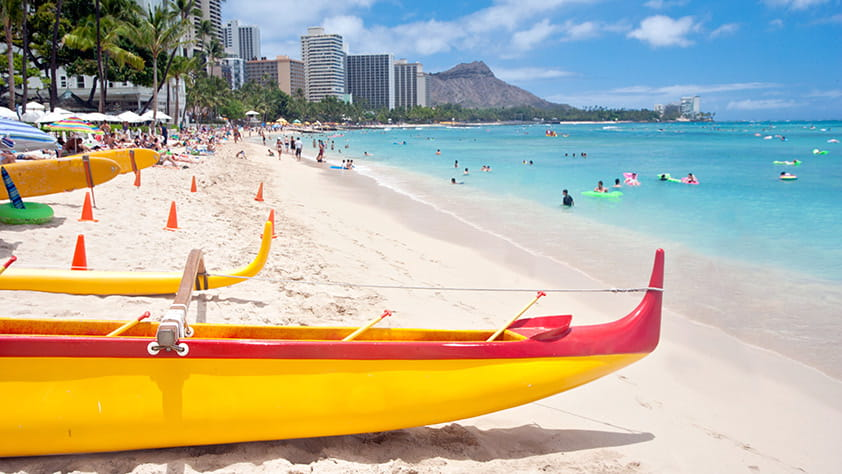 Bright yellow and red outrigger canoes on Waikiki beach