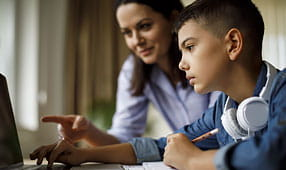 Mother Helping Teenager with Homework on a Laptop