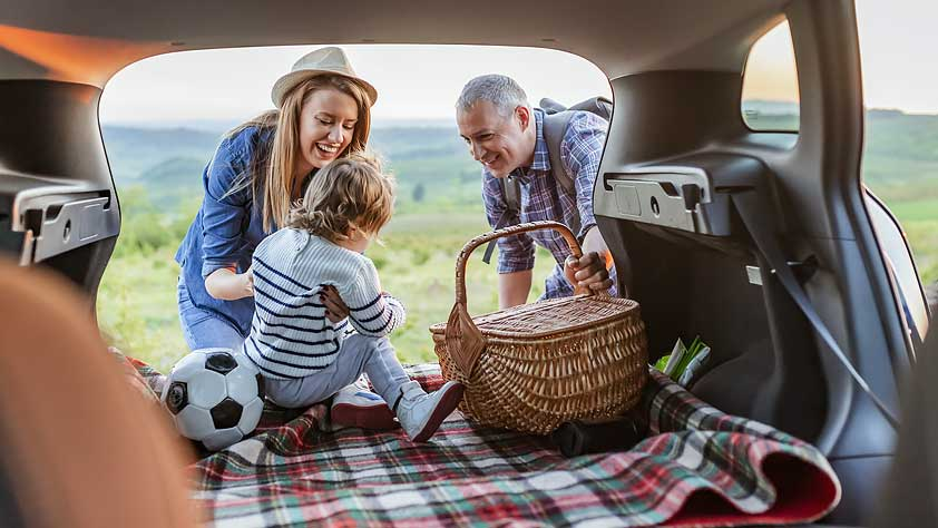 Do You Have Questions About Traveling During the Coronavirus Crisis - Couple and Young Child in the Back of a Car With a Picnic Basket