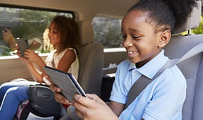 Two Happy Children Sitting in a Car Reading From Tablets