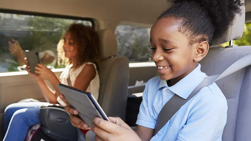 Easy Ways to Keep Your Kids Happy on a Family Vacation - Two Children Sitting in a Car Reading From Tablets