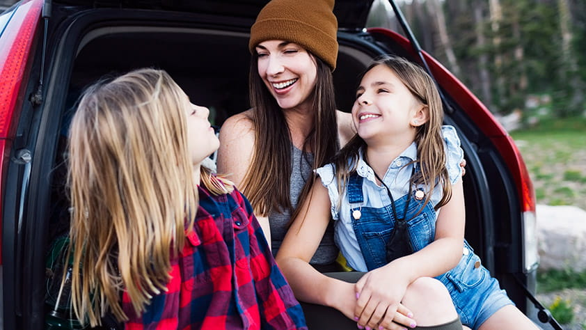 Mother and Daughters Laughing and Sitting in the Trunk of a Hatchback Car